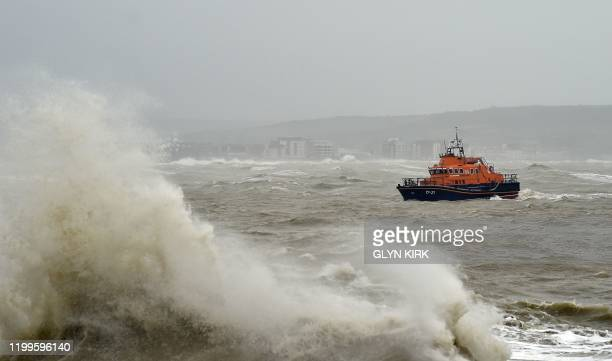 The RNLI Nehaven lifeboat is seen beyond waves as they crash into the sea wall at Newhaven Harbour on the south coast of England on February 9 as...