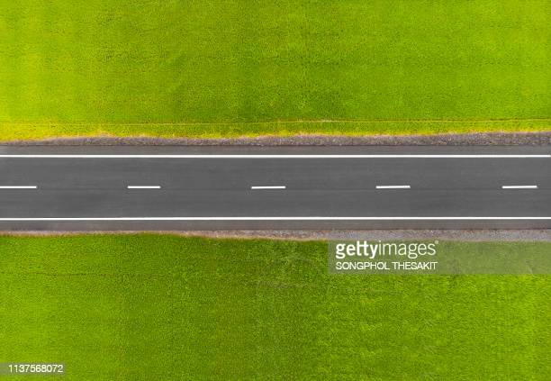 the road in the middle of the field./aerial shot - haut photos et images de collection