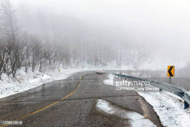 the road in the mist on a snowy day - gangwon province stock pictures, royalty-free photos & images