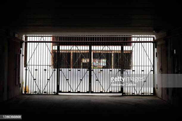 the road in the tunnel leading to a closed gate and a dead end. - weathered stock pictures, royalty-free photos & images