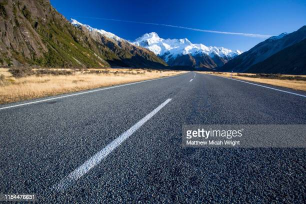 the road leading into the mount cook national park. snowcapped mountains appear at the end of the road. - dividing line road marking stock pictures, royalty-free photos & images