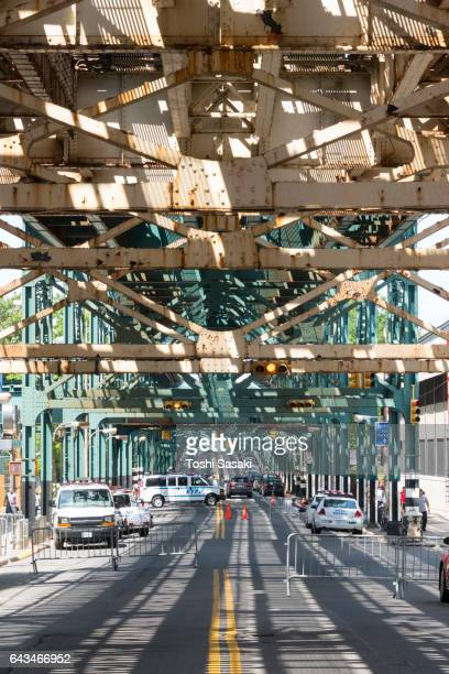 The road runs under the elevated subway line at The Bronx New York.
