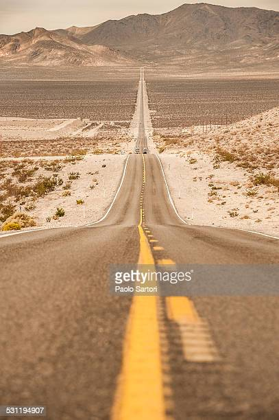 The road that leads to Death Valley from Beatty is lost on the horizon in the desert plain. Beatty, Nevada.