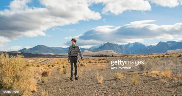 The road trip. Young man, travelling hipster, looking around on the desert road in Nevada at sunset