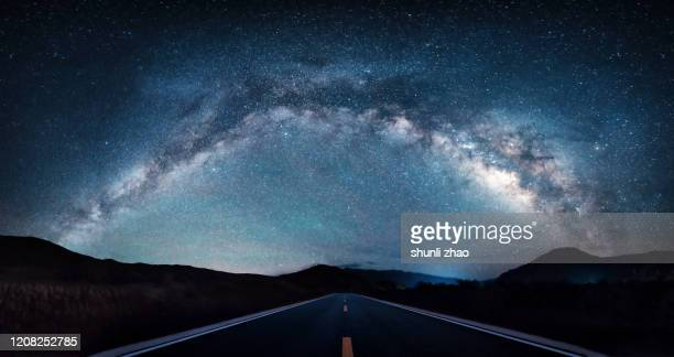 the road under the milky way arch bridge - high dynamic range imaging stock pictures, royalty-free photos & images