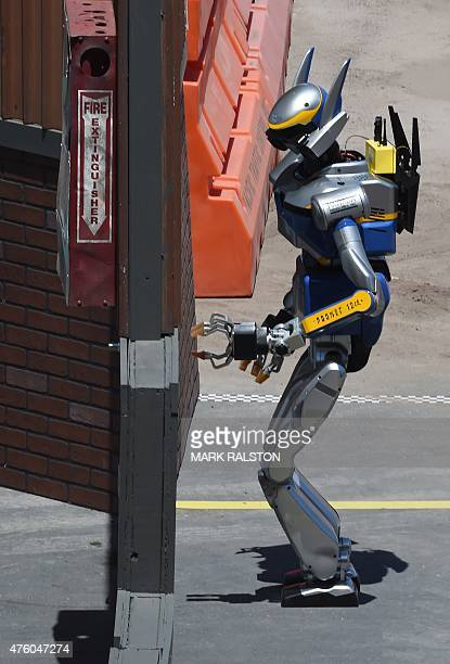 The robot named 'HRP2 Kai' developed by Team AISTNEDO from Japan attempts to open a door during the finals of the DARPA Robotics Challenge at the...