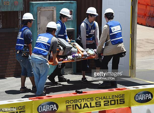 The robot named 'Jaxon' developed by Team NEDOJSK from Japan is carried out on a stretcher after falling during the finals of the DARPA Robotics...