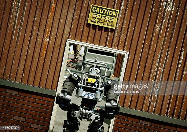 The robot named 'WalkMan' developed by Italian University of Pisa team passes through a door during the finals of the DARPA Robotics Challenge at the...