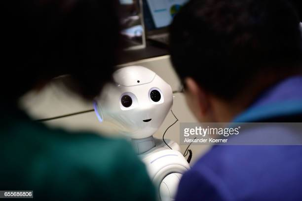 The robot 'Pepper' speaks with visitors at the IBM stand at the CeBIT 2017 Technology Trade Fair on March 20 2017 in Hanover Germany 'Pepper' has a...