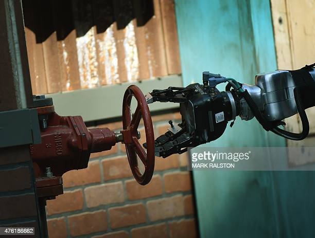 The robot 'Warner' developed by Team WPICMU from the US opens a valve during the finals of the DARPA Robotics Challenge at the Fairplex complex in...