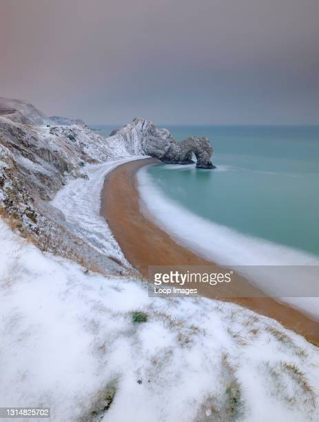 The rock arch of Durdle Door covered in snow.