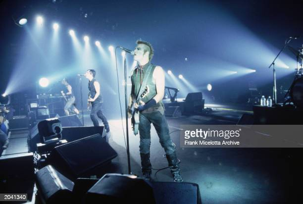 The rock band Nine Inch Nails performs in concert 2000 Singer and singwriter Trent Reznor sings at center stage flanked by an unidentified bassist...