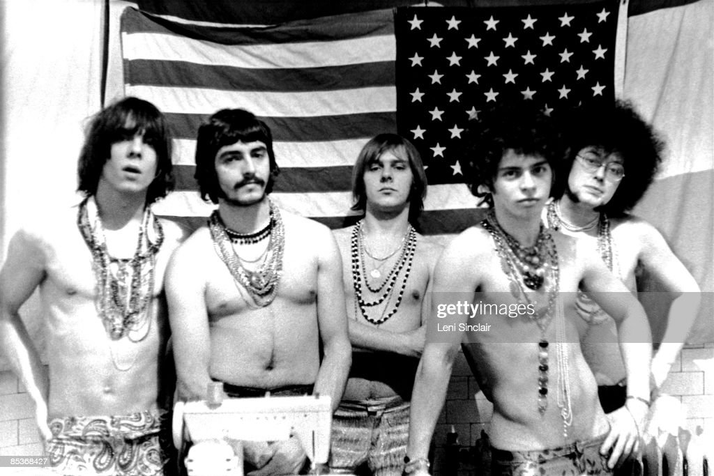 The rock group MC5 (L-R Fred 'Sonic' Smith, Dennis 'Machine Gun' Thompson, Rob Tyner, Wayne Kramer and Michael Davis) pose for a photo in front of an American flag in 1967 in Detroit, Michigan.