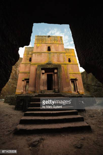 the rock hewn bet giyorgis framed by a passageway entering the courtyard, lalibela, ethiopia - lalibela stock photos and pictures