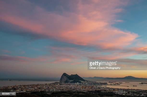 The Rock of Gibraltar below a dusk sky, with Jebel Musa Mountain and the North African coast visible across the Strait of Gibraltar