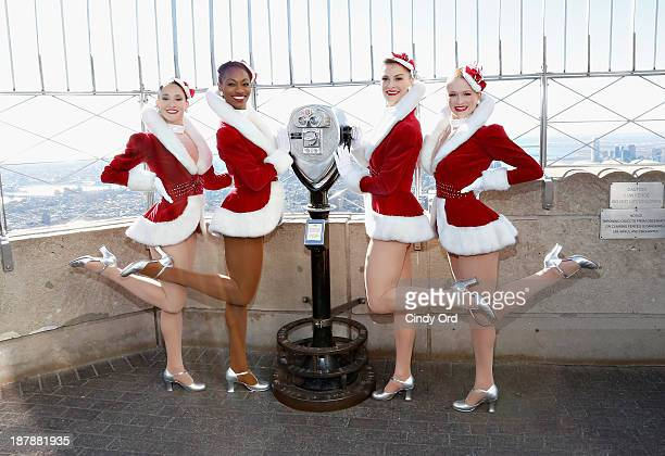 The Rockettes light the Empire State Building green and red in celebration of the '2013 Radio City Christmas Spectacular' opening night on November...