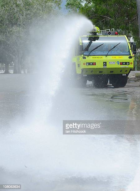 The Rockhampton airports fire rescue truck uses its water canon to wash down flood affected streets as flood waters fall on January 16 2011 in...