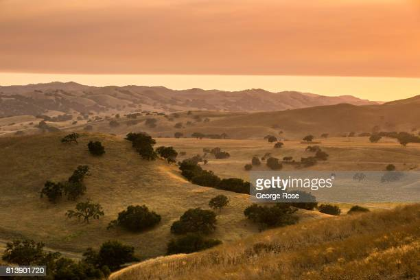 The rolling hills in Foxen Canyon are viewed near sunset with heavy smoke from nearby fires on July 9 near Los Olivos California Because of its close...