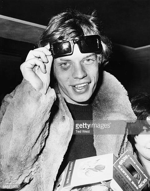 'The Rolling Stones' lead singer Mick Jagger lifting up his sunglasses to reveal a black eye which he received on tour in France as he signs...
