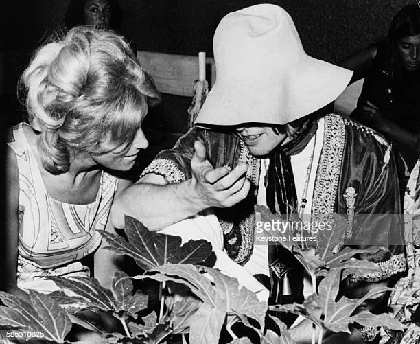 'The Rolling Stones' musician Brian Jones is hidden from the camera by his hat as he talks to model Suki Potier Marbella Spain 1967