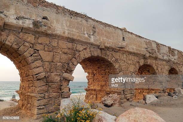 the roman aqueduct by the sea - römisch stock-fotos und bilder