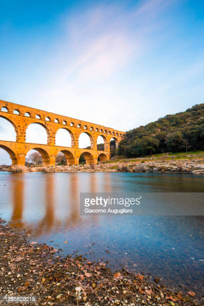 the roman aqueduct pont du gard reflected in the water, nimes, provence, france - pont du gard stock pictures, royalty-free photos & images