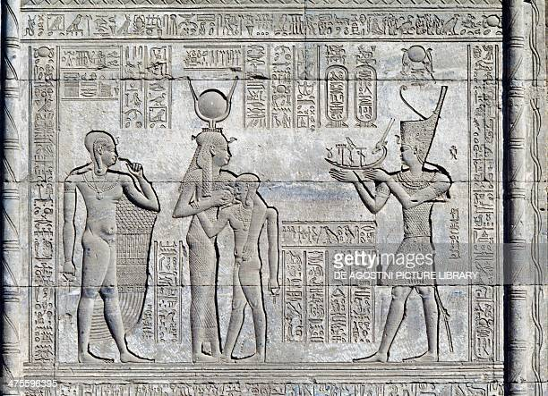 The Roman Emperor Trajan depicted as a pharaoh offering a votive boat to the Goddess Hathor who is nursing the young Ihi, and the growth of God Ihi...