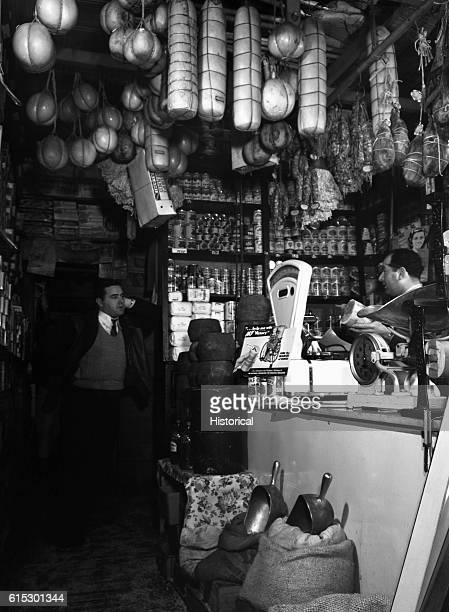 The Ronga brothers Italian grocers stand amidst their goods in their store on Mulberry Street New York New York January 1943