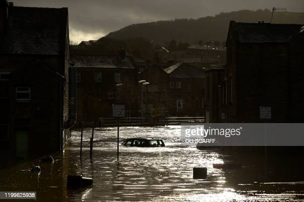 The roof of a submerged car is pictured in a flooded street in Mytholmroyd northern England on February 9 after the River Calder burst its banks as...