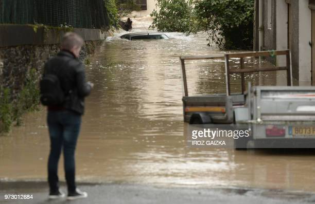 The roof of a submerged vehicle is seen after flood waters sweep through the streets following heavy rains in SaliesdeBearn south western France on...