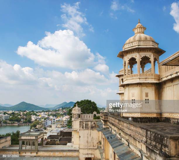 The rooftop cupolas and terraces of historical City Palace in Udaipur, India overlooks famous Lake Pichola on a sunny day