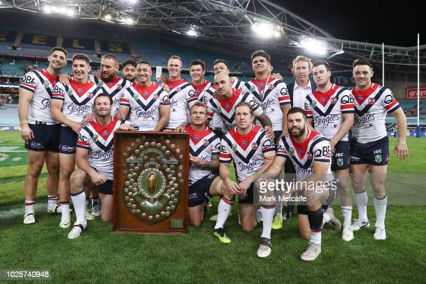 The Roosters team pose with the JJ Giltinan Shield for winning the minor premiership during the round 25 NRL match between the Parramatta Eels and...