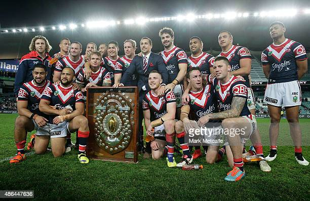 The Roosters team pose with the JJ Giltinan Shield for winning the minor premiership during the round 26 NRL match between the Sydney Roosters and...