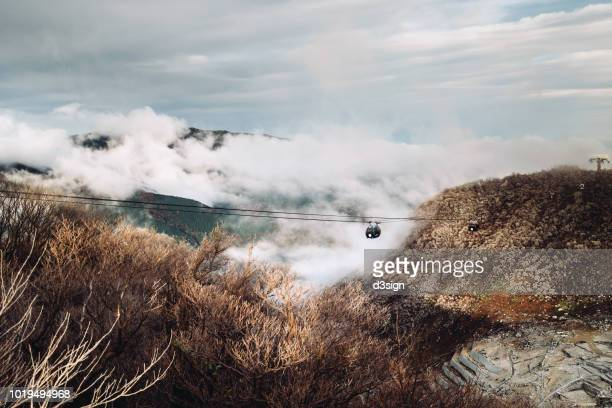 the ropeway riding above the rising volcanic fumes of owakudani, hakone - fuji hakone izu national park stock photos and pictures