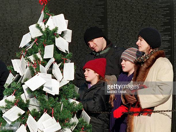 The Rosenberg family from Oakland CA from left Alexa Bill Ariane and Kathi read Christmas cards 21 December 2000 placed on a tree in front of the...