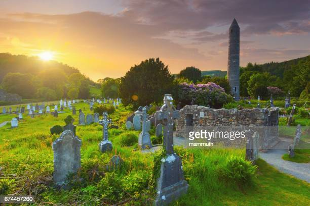 the round tower and the cemetery at the glendalough monastic site in country wicklow, ireland - irish round tower stock photos and pictures