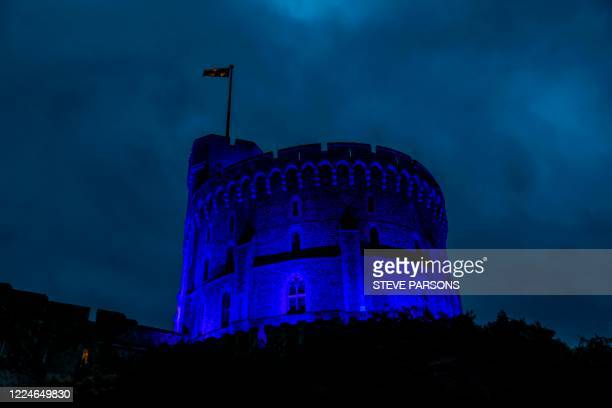 The Round Tower at Windsor Castle, where Britain's Queen Elizabeth II is living due to the COVID-19 pandemic, is pictured illuminated blue on July 3...