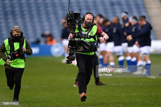 The roving Television Cameraman breaks into a run whilst wearing a face covering during the Guinness Six Nations match between Scotland and Italy at...