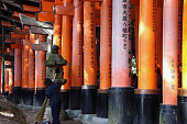 http://www.istockphoto.com/photo/the-row-of-torii-and-stone-lantern-with-sweeper-at-japanese-shrine-gm892842212-247055850