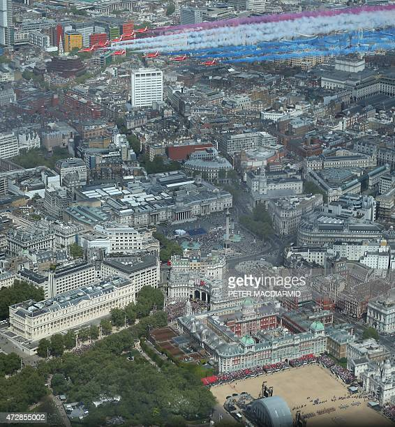 The Royal Air Force Aerobatic Team, the Red Arrows, conduct a flypast as members of the armed forces and venterans muster below on Horse Guards...