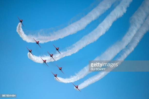 TOPSHOT The Royal Air Force Aerobic Team the Red Arrows perform an aerobatic display during the national Armed Forces Day celebrations at Llandudno...