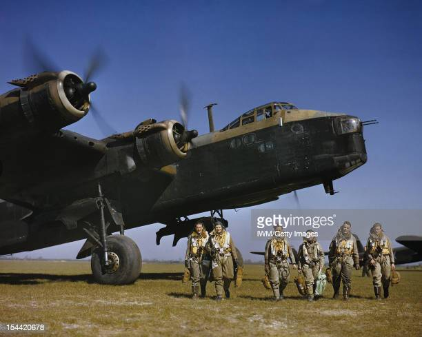 The Royal Air Force In Britain Spring 1942 Aircrew in full flying kit walking beneath the nose of Short Stirling Mark I N3676 'S' of 1651 Heavy...