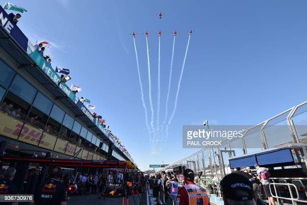 TOPSHOT The Royal Australian Airforce Roulettes perform an aerial display over the pit lane as Red Bull's Dutch driver Max Verstappen prepares for...