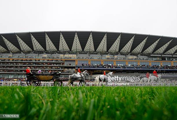 The Royal Carriage procession makes it way up the straight mile past the grandstand on Ladies' Day during day three of Royal Ascot at Ascot...