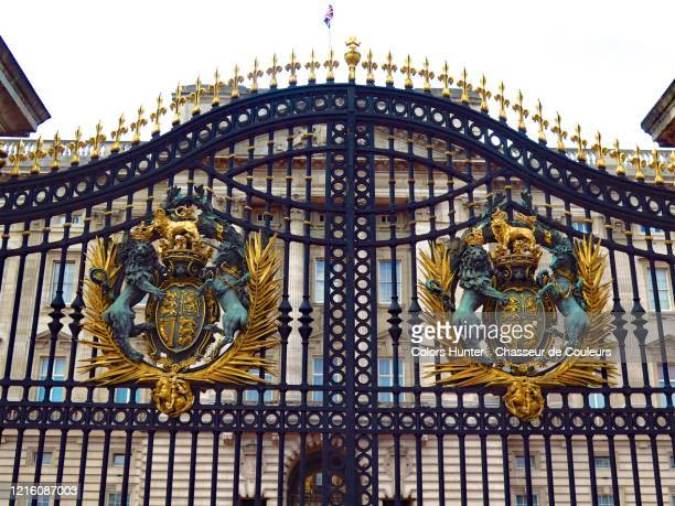 the royal coat of arms on the gates of buckingham palace - buckingham palace crest stock pictures, royalty-free photos & images