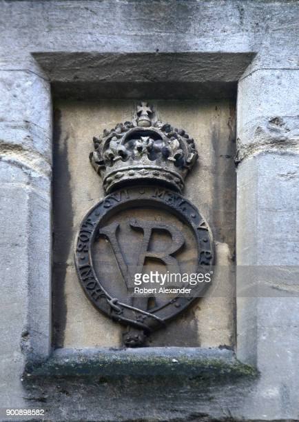 The royal crest and monogram of Queen Victoria is carved in stone in the wall surrounding Windsor Castle in Windsor England Windsor Castle is a...