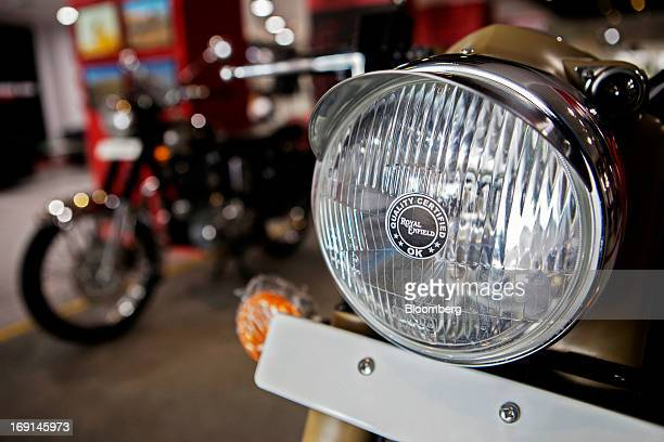 The Royal Enfield logo is displayed on the headlight of a Desert Storm motorcycle on display at the Eicher Motors Ltd Royal Enfield flagship...