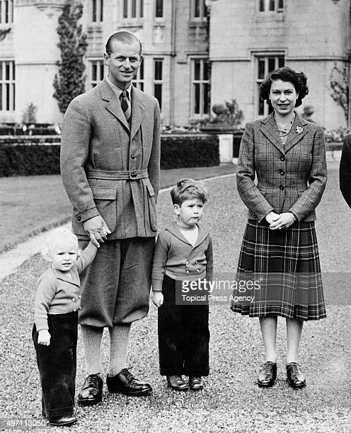 The royal family in the grounds of Balmoral Castle in Scotland, 26th September 1952. From left to right, Princess Anne, the Duke of Edinburgh, Prince...