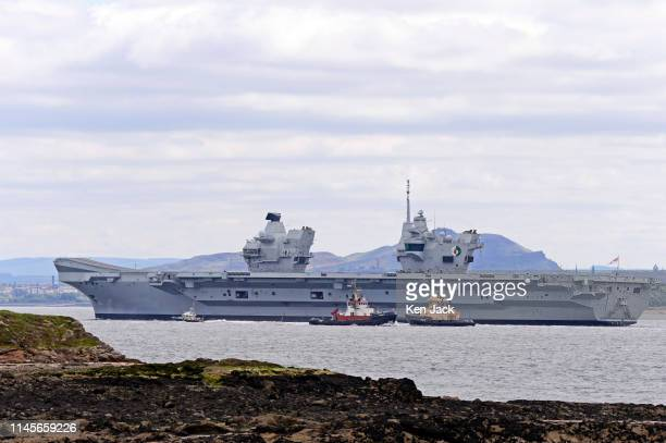 The Royal Navy aircraft carrier HMS Queen Elizabeth sails from the Forth Estuary with the Edinburgh skyline in the background following a period of...