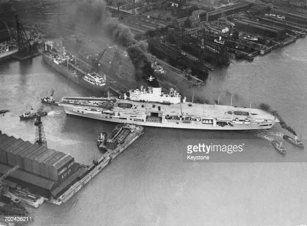 The Royal Navy Audaciousclass fleet aircraft carrier HMS Ark Royal is maneuvered out by tugboats from the Cammell Laird shipyard in Birkenhead...
